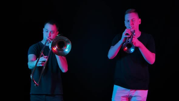 Male Musicians Play the Trombone and Trumpet in the Studio on a Black Background in Neon Light