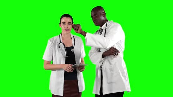 a Caucasian and African American people wearing a surgeon blouse and scrumbs in a green
