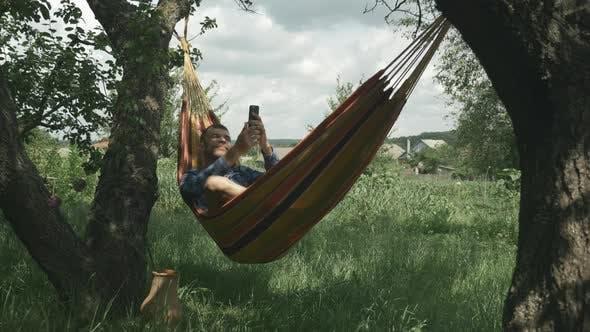 Man taking selfie photo with mobile phone lying on hammock. Male takes selfies on smartphone