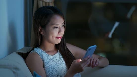 Thumbnail for Woman look at smart phone at night