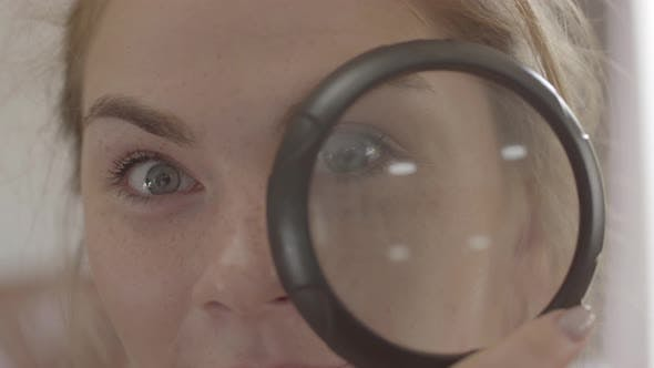 Thumbnail for Pretty Girl with Blue Eyes Looking in the Camera Through the Loupe Close-up. Positive Lifestyle