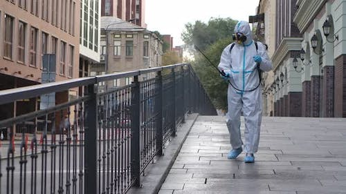 A Working Man in a Protective Suit and a Respirator Disinfects, Sprays Chemicals on the Surface of