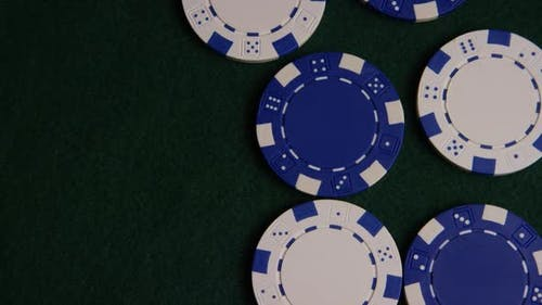 Rotating shot of poker cards and poker chips on a green felt surface - POKER 037