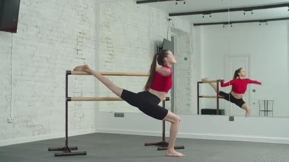 Sportliche Frau macht Barre Workout im Fitnessstudio
