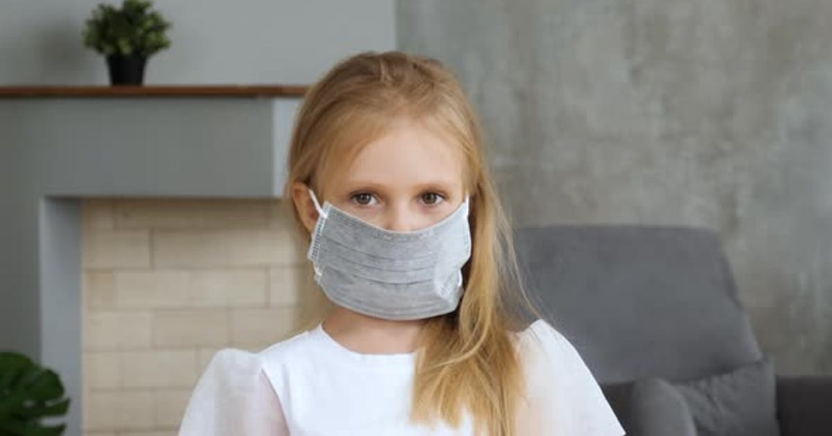 Girl wearing medical mask and looking to camera