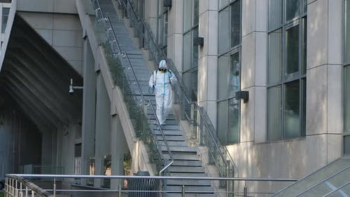 A Professional Cleaner in a Protective Suit and a Respirator Disinfects Outdoor Covid-19. Corona