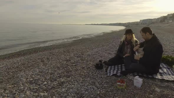 Thumbnail for Couple opening bottle of wine, romantic picnic by seaside in Nice, France, love