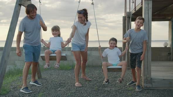 Thumbnail for Big Cheerful Family Having Fun on a Swing.