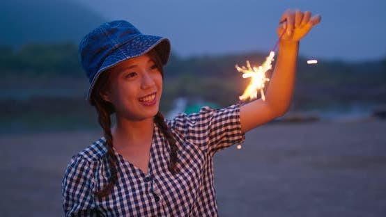 Thumbnail for Woman play with sparklers in the summer time at outdoor