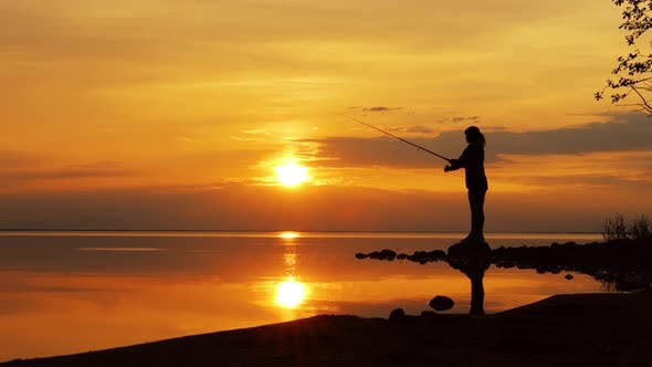 Thumbnail for Woman Fishing on Fishing Rod Spinning at Sunset Background.