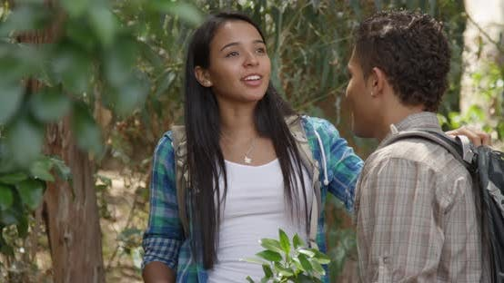 Happy Hispanic man flirting with girlfriend outdoors