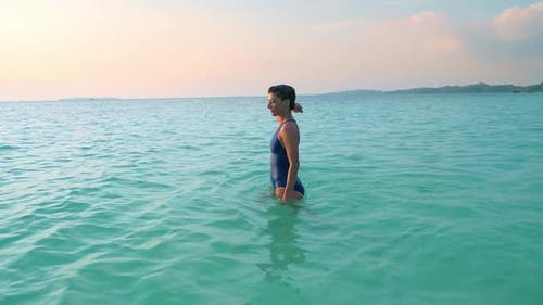 Slow motion: woman swimming in turquoise water sunset sunburst backlight tropica