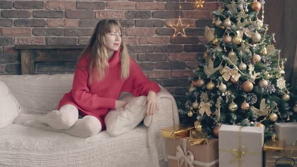 Young Blond Woman in Red Sweater Sits Near Christmas Tree