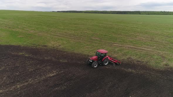 Tractor with Disc Harrows on the Farmland. Summer, cloudy
