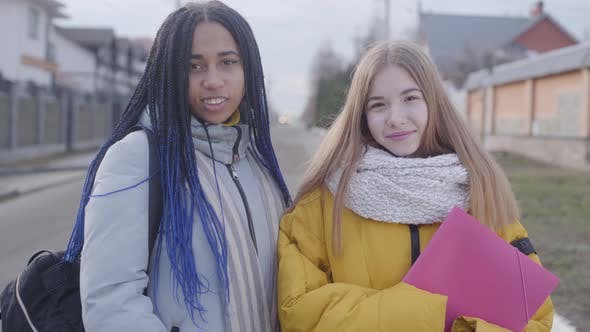 Thumbnail for Portrait of Two Beautiful Girls Looking at Camera and Smiling. Caucasian and African American Teens