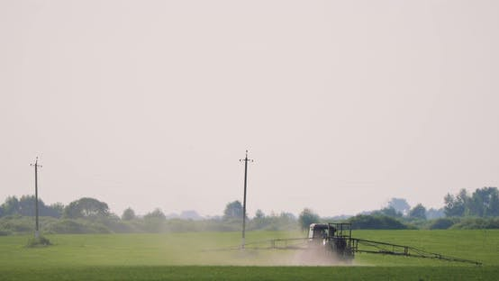Traktor mit Düngerstreuer sprüht Pestizide oder Chemikalien auf Feld mit Sprüher am Frühling