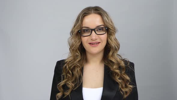 Thumbnail for Portrait of Girl in Bussines Suit Fixing Her Glasses and Raising Eyebrow Looking at Camera