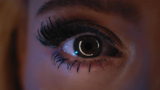 Thumbnail for Close up of woman's eye with beautiful party make up opening in studio lighting