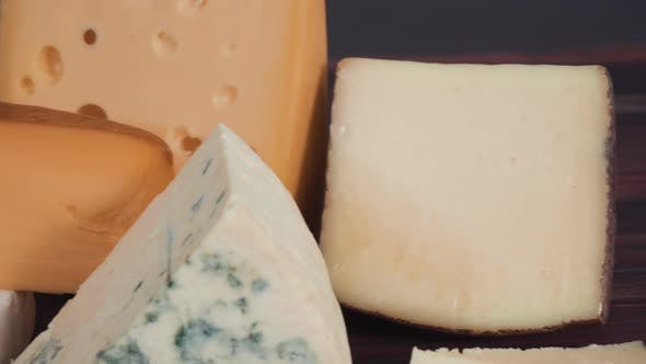 Thumbnail for Large wedges of gourmet cheese on a rustic wood background.
