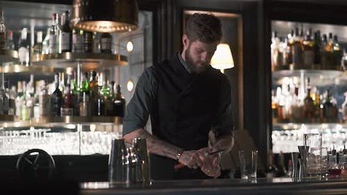 Tall Bearded Bartender Crushing Big Piece of Ice with the Knife Standing at the Bar Counter