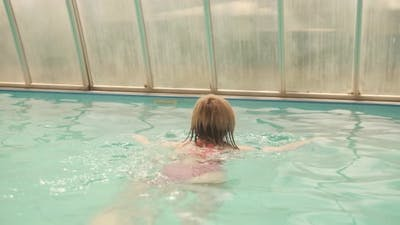 The woman swims in the pool. Swimming is good for health