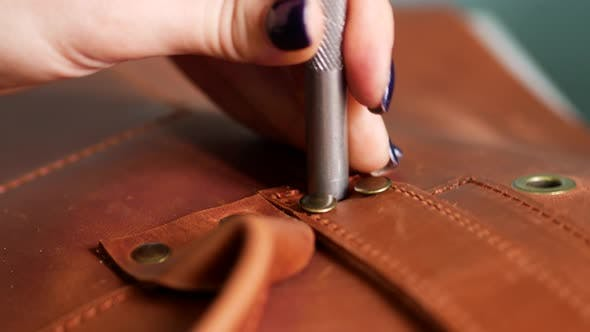 Female Worker Puts Rivets on Leather Bag Straps with Chisel and Hummer. Crafted Handmade