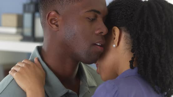 Thumbnail for Young black man holding girlfriend and whispering into her ear