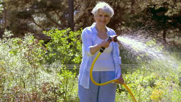 Senior Woman Watering Lawn By Hose at Garden 36