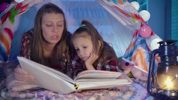 Thumbnail for Family Bedtime, Mom And Child Daughter Reading Book In Tent