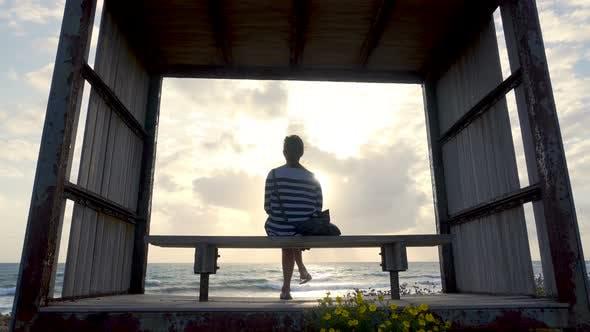 Thumbnail for mädchen auf einer bank durch die seashore auf sonnenuntergang