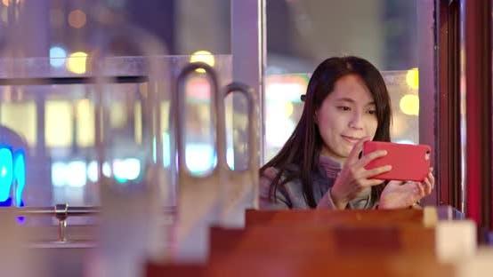 Woman take photo on tram