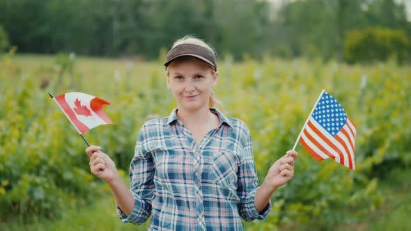 Thumbnail for Young Woman Farmer Holding the USA Flag on One Side and the Canada Flag on the Other.