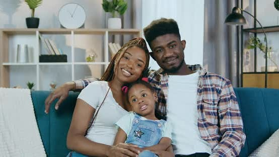Cheerful Afro American Family Relaxing on couch