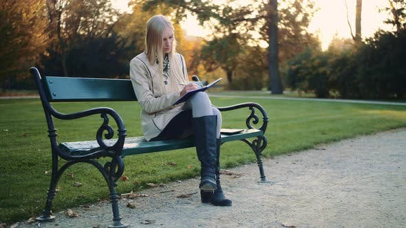 Thumbnail for Young Woman Is Writing a Diary Outdoors in the Park