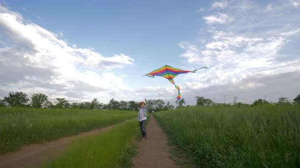 Thumbnail for Running Little Boy in Hat and Shirt Plays with Flying Kite at Green Field on Background of Sky