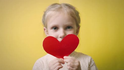 Little girl with valentine on yellow background