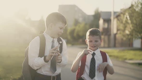 CU, Tracking: Zwei Schüler gehen nach der Schule nach Hause, sie reden, sie halten ein Smartphone in ihren Händen.