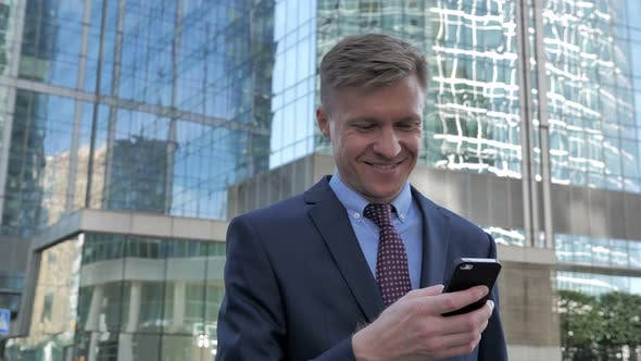 Thumbnail for Walking Businessman Text Messaging on Smartphone