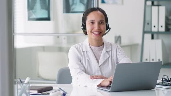 Thumbnail for Fröhliche Ärztin im drahtlosen Headset posiert für Kamera am Schreibtisch in der Klinik