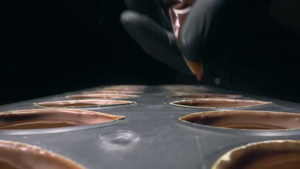 Cover Image for Chocolatier Fills Chocolate Molds with Liquid Chocolate Filling for Praline Sweets , Making of