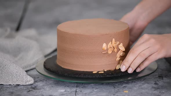Female Pastry Chef Prepares a Cake and Decorates It with Almond Flakes