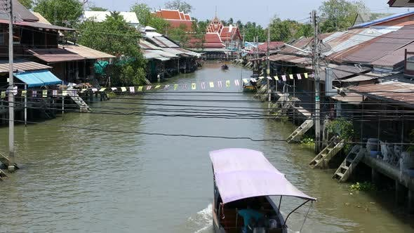 Thumbnail for Overview from the Tha Kha Floating Market with a boat passing by