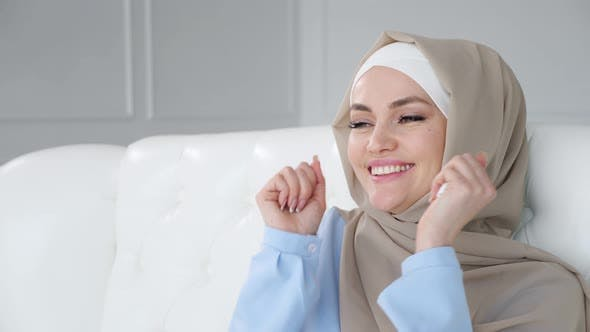 Happy Young Muslim Woman Wearing Hijab Is Dancing Sitting on Sofa and Listening Traditional Music.