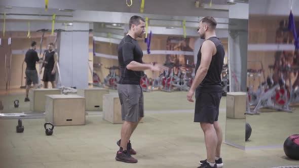 Wide Shot von zwei Bodybuildern, die im Fitnessstudio sprechen. Starke kaukasische Sportler stehen im Sportverein