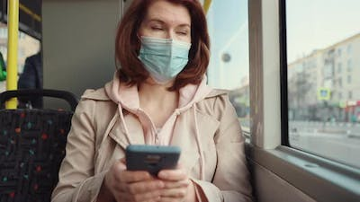 Woman Sitting in Bus and Using Smartphone