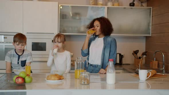 Sleepy Children and Babysitter Having Breakfast in Kitchen Cereal Milk and Juice