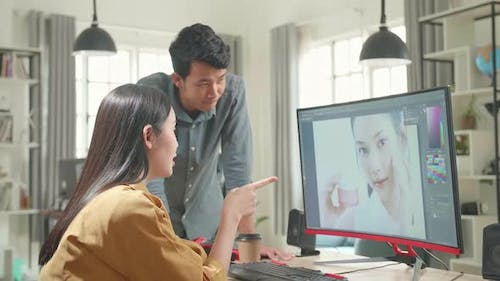 Male Art Director Consults Designer Colleague, They Work On A Portrait In Photo Editing Software