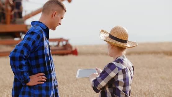 Female Farmer Discussing With Businessman On Farm