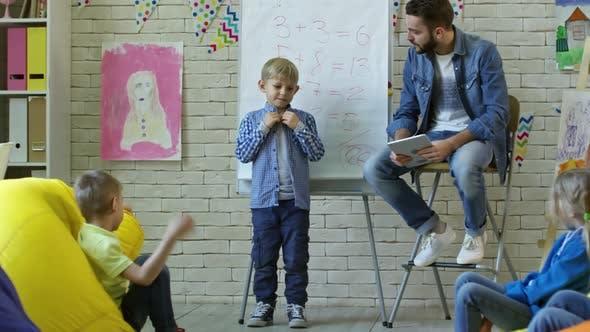 Cute Boy Speaking in Front of Classmates in Kindergarten