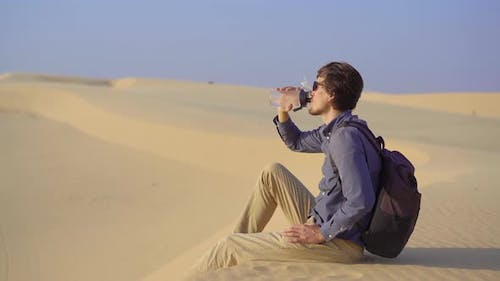 A Man Sitting on a Dune in a Desert Drinks Water From a Reusable Bottle